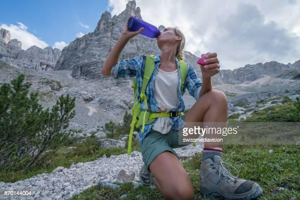 Femelle de randonneur à boire sur la montagne sentier, Dolomites, Italie