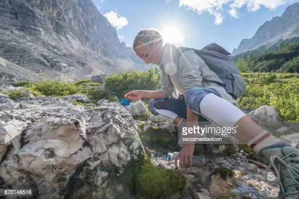 Wanderer weibliche Füllung Kürbis aus frischen Stream auf Mountain Trail, Dolomiten, Italien