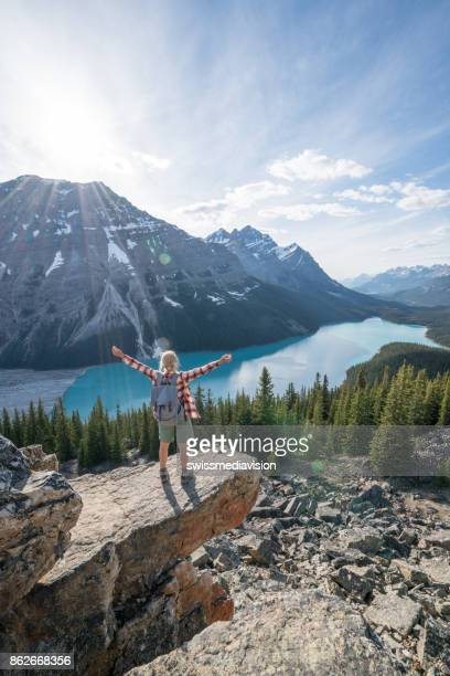 Hiker female on mountain top celebrating achievement