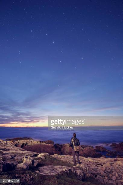 Hiker gazing at the Big Dipper from rocks, Fogo Island, Newfoundland, Canada