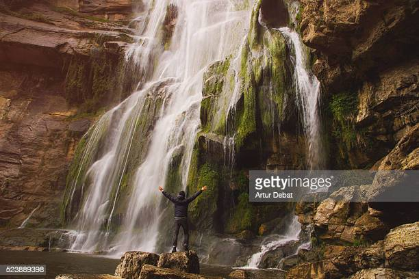 Hiker guy exploring a beautiful 100 meters tall waterfall with curtain of water over the crag during the rainy season in the Catalan mountains during a outdoor adventure.