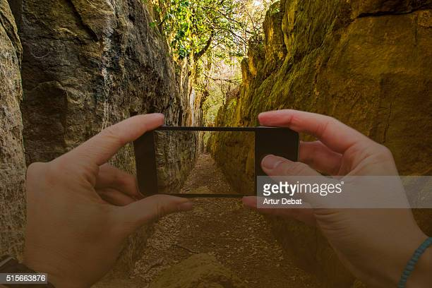 Hiker guy taking pictures from personal point of view with smartphone of a beautiful crack between two walls in a hidden place with nice narrow path of the mountain landscape in the Garrotxa region.