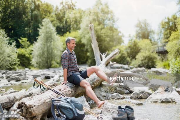 Hiker having a break at the riverbank splashing his feet in water