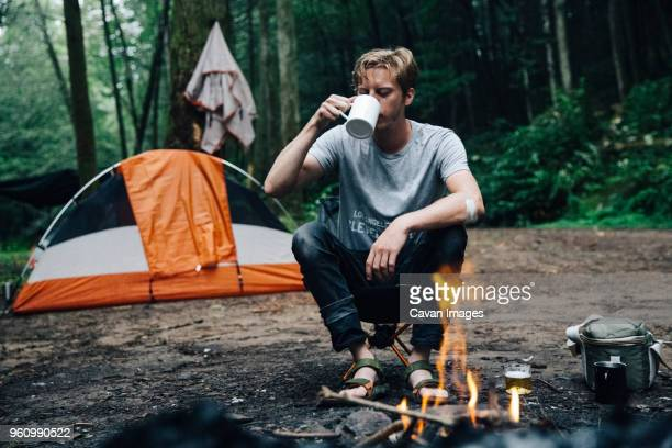 hiker having drink at campsite in forest - man on fire stock photos and pictures