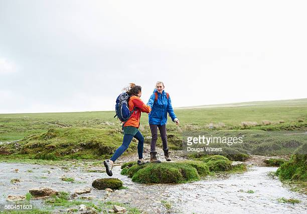 hiker helping friend across stream - dougal waters stock pictures, royalty-free photos & images