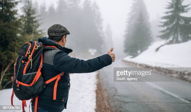 hiker hitchhiking - hitchhiking stock pictures, royalty-free photos & images