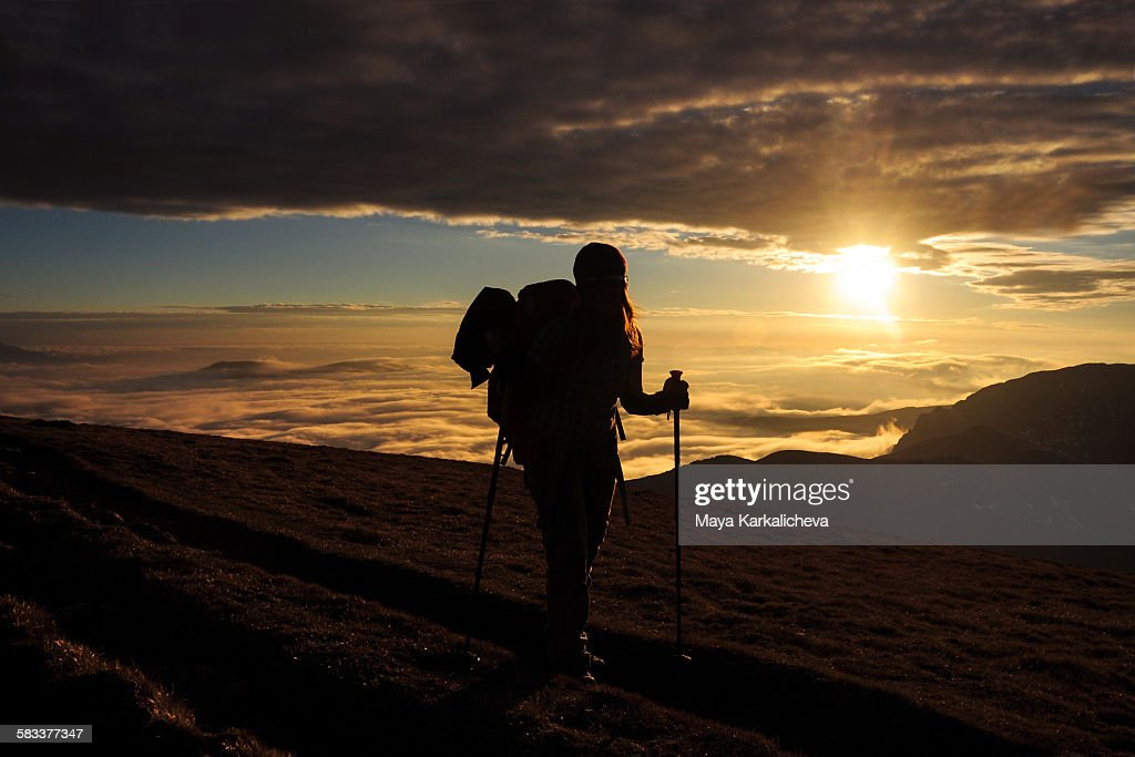 Hiker in a mountain above the clouds : Stock Photo