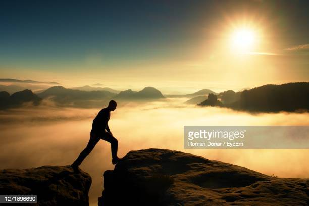 hiker in black is jumping between the rocky peaks. wonderful daybreak in rocks. miracle of nature - life events stock pictures, royalty-free photos & images