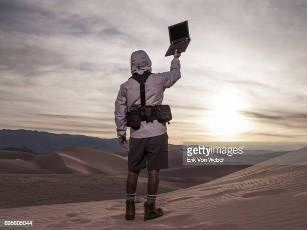 hiker in desert holds laptop high looking for wireless connection