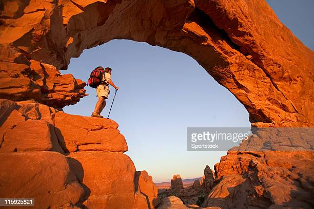 hiker in rock arch looking at view - moab utah stock photos and pictures