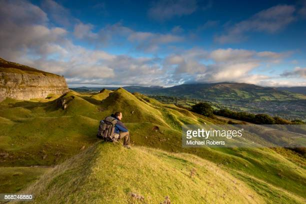 Hiker in the Llangattock escarpment quarries looking towards Crickhowell, in the  Brecon Beacons national park, Wales