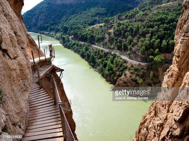 hiker in the nature walking on a wooden footbridge, nailed on the walls of rock in a gorge to great height. - caminito del rey fotografías e imágenes de stock