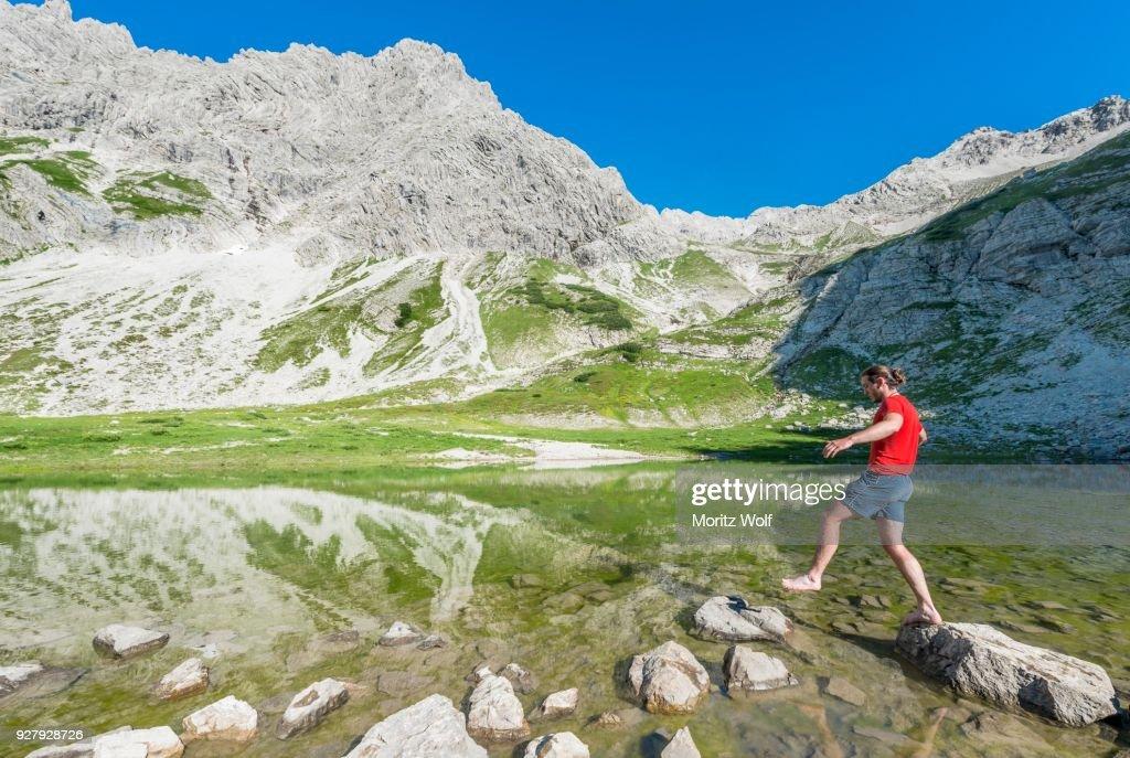 Hiker Jumping On A Stone Mountain Lake At The Printz Luitpolt House