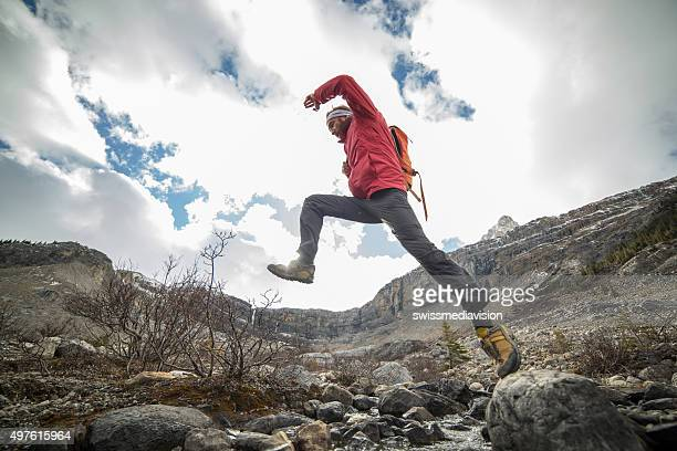 Hiker jumping over mountain river