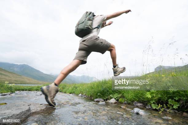 hiker jumps over river - the way forward stock photos and pictures