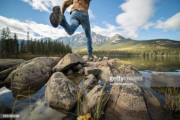 para excursionistas jumps rock en el lago de montaña rock - alberta fotografías e imágenes de stock