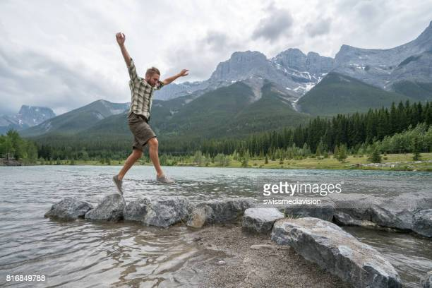 hiker jumps rock to rock on mountain lake - kananaskis country stock pictures, royalty-free photos & images