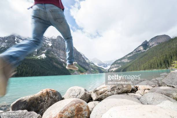 Hiker jumps rock to rock on mountain lake