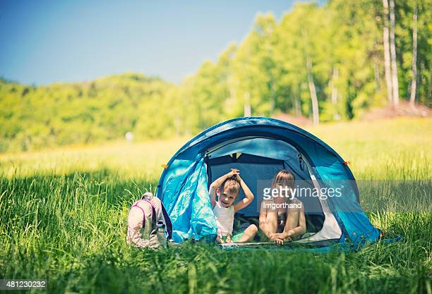 Hiker kids having fun in tent in the forest