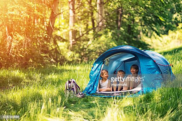hiker kids sitting in tent in the forest - camping stock photos and pictures