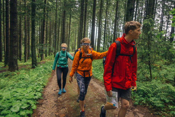 Hiker leads blindfolded companions along forest trail