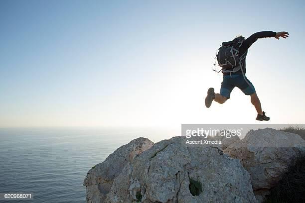 Hiker leaps between boulders on summit