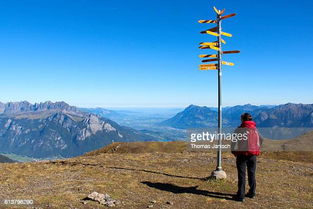 Hiker looking at a signpost at Pizol mountain
