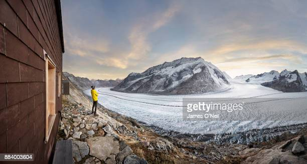 Hiker looking at glacier at sunset, Aletsch Glacier, Switzerland