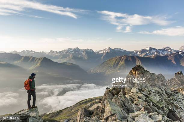 hiker looking at mountain range - european alps stock photos and pictures