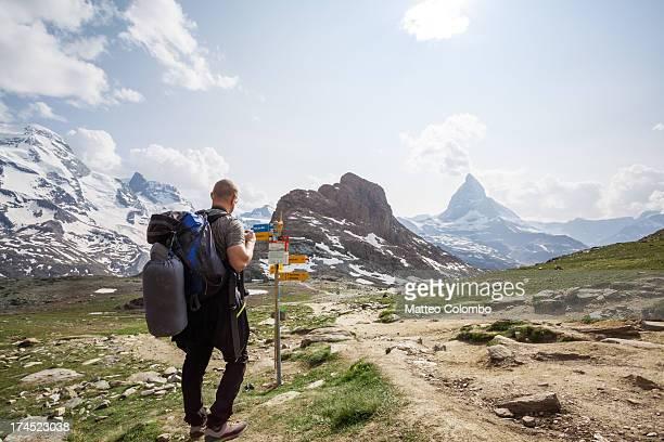Hiker looking at mountain signpost near Matterhorn