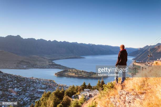 hiker looking at queenstown from lookout at sunrise, new zealand - queenstown stock pictures, royalty-free photos & images