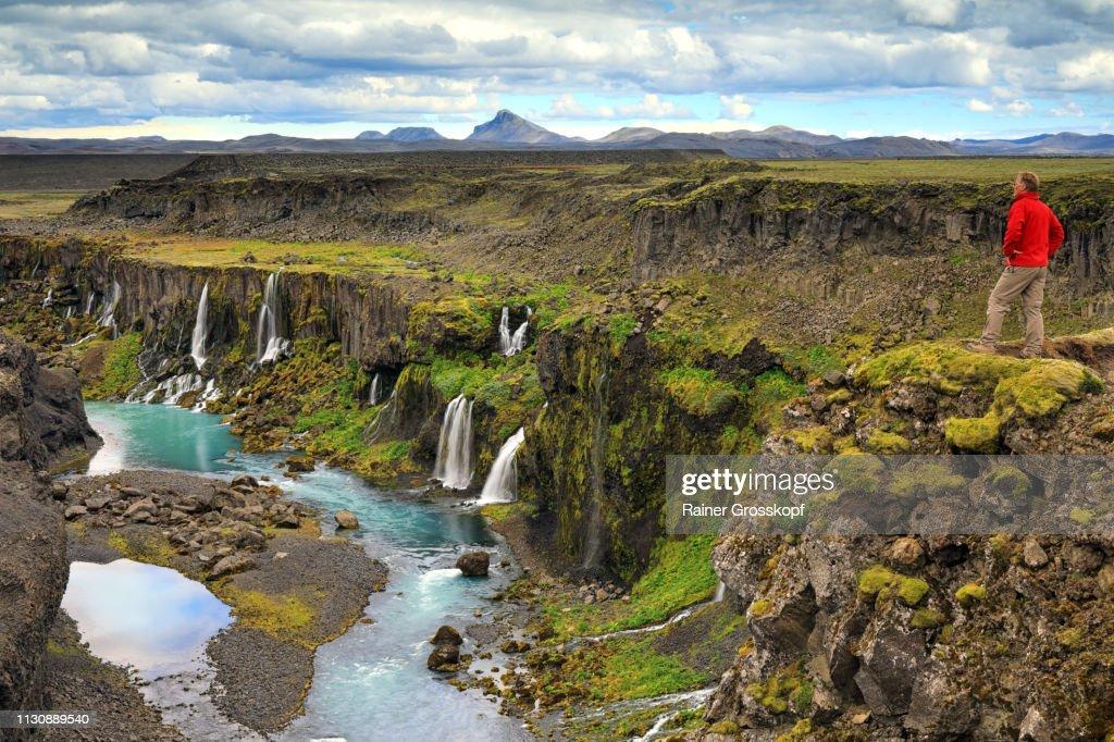 Hiker looking at Sigöldugljufur gorge with several waterfalls : Stock-Foto