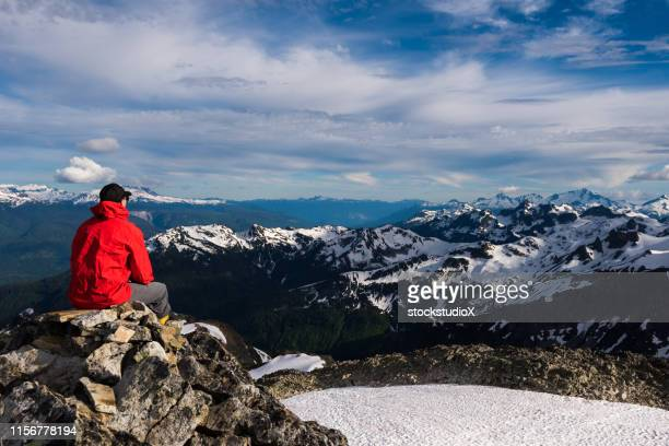 hiker looking at snow covered mountains - red jacket stock pictures, royalty-free photos & images