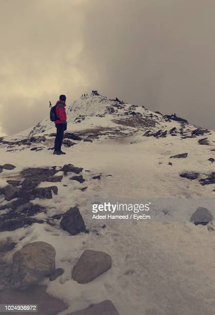 Hiker Looking At Snowcapped Mountain Against Sky