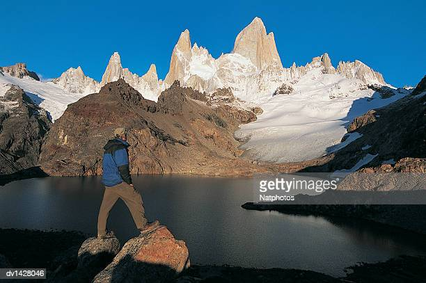 hiker looking at the view of lagos de los tres with mt fitzroy in the background, glacier national park, patagonia, argentina - três pessoas stock pictures, royalty-free photos & images