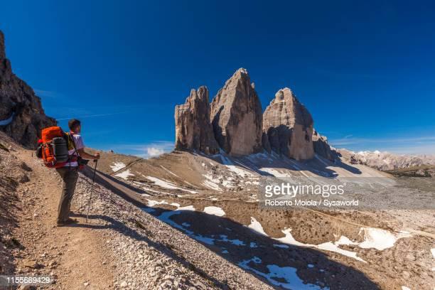 hiker looking at tre cime di lavaredo, dolomites, italy - トレチーメディラバレード ストックフォトと画像