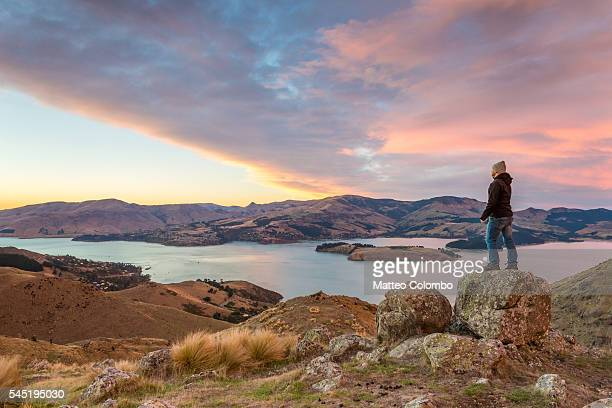 Hiker looking at view at sunrise, Littleton bay, New Zealand