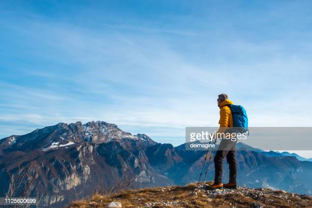 hiker looking at view from high path mountain - padded jacket stock pictures, royalty-free photos & images