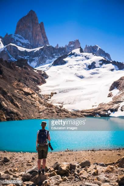 Hiker looking at view of Mount Fitz Roy, the glacier and Lago de los Tres, El Chalten, Patagonia, Argentina, South America.