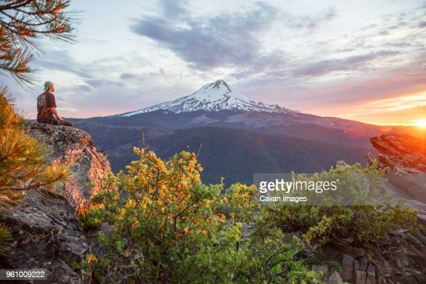 hiker looking at view while sitting on mountain during sunset - mt hood stock pictures, royalty-free photos & images