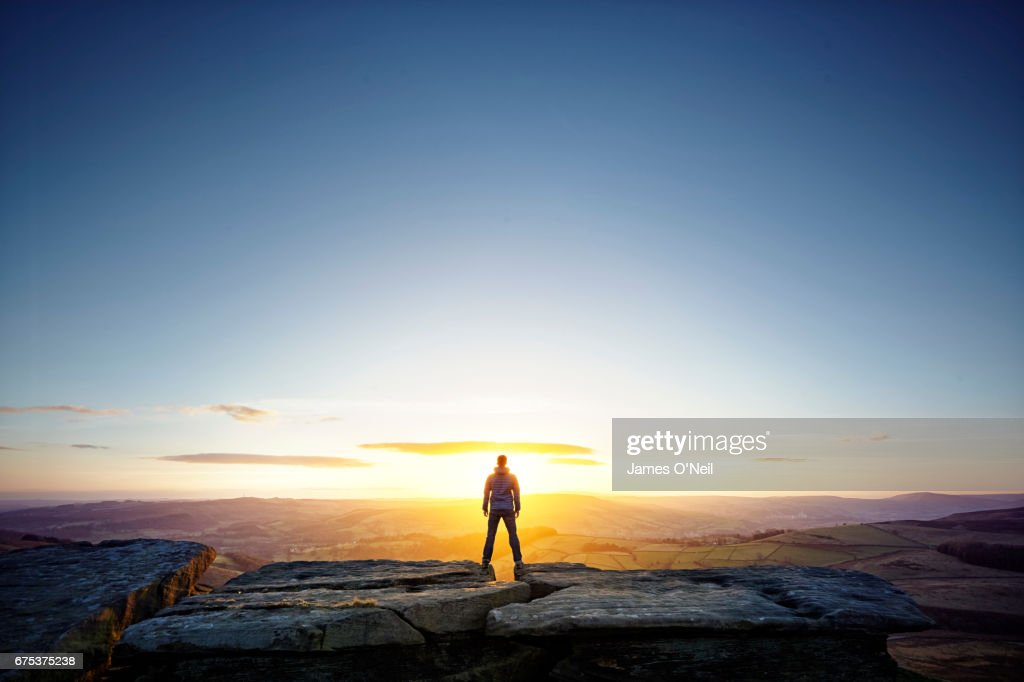 Hiker looking out at sunset from behind : Stock Photo