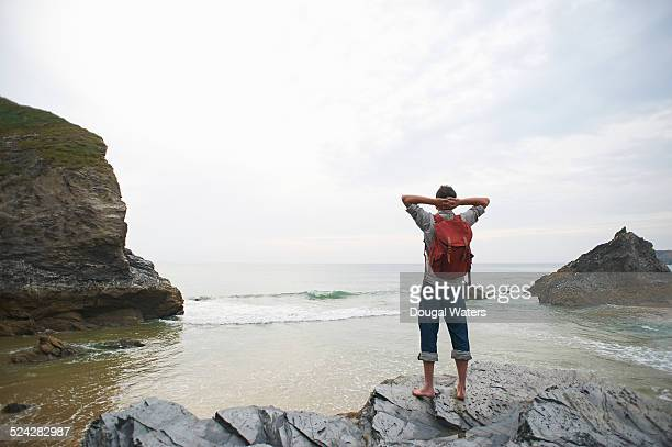 Hiker looking out to sea from rocky coastline.
