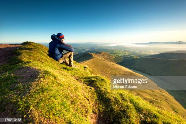hiker looking over the brecon beacons from pen y fan - lifestyles stock pictures, royalty-free photos & images