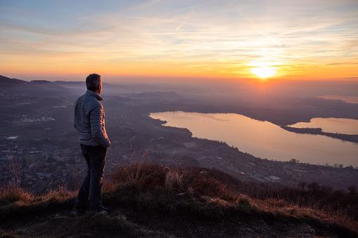 Hiker looking sun over horizon 1124629093