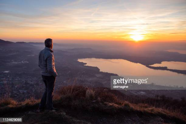 hiker looking sun over horizon - contemplation stock pictures, royalty-free photos & images