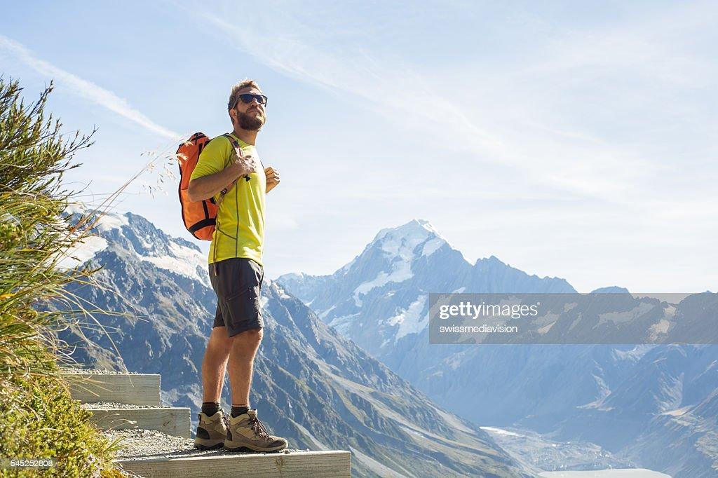 Hiker looks at mountain peak : Stock Photo