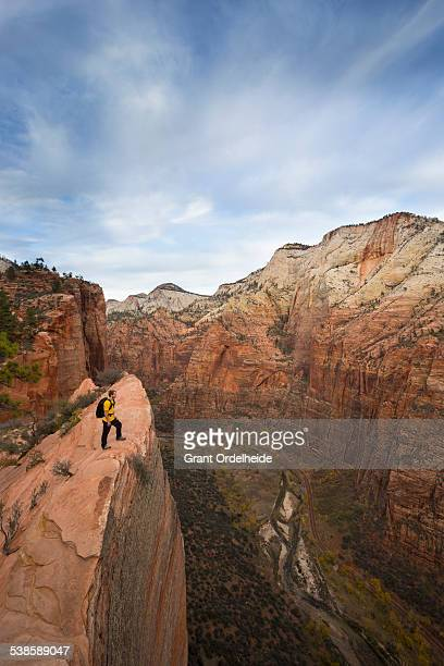 A hiker looks out over Zion from the Angels Landing trail.