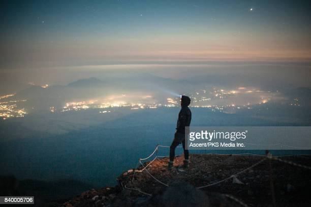 Hiker Looks over City on side of Mountain