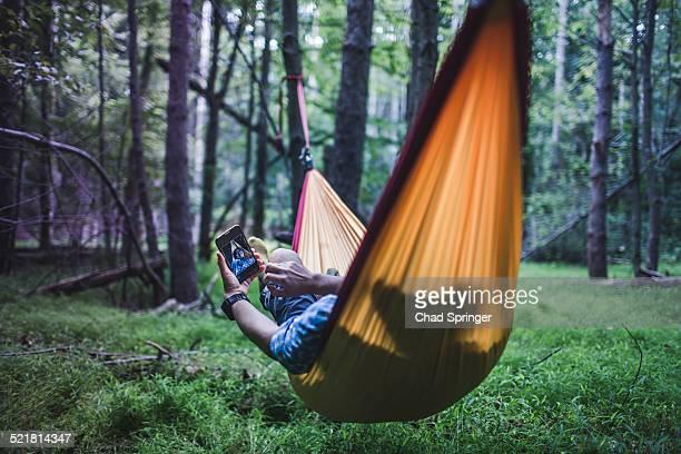 Hiker lying in hammock in forest using digital device
