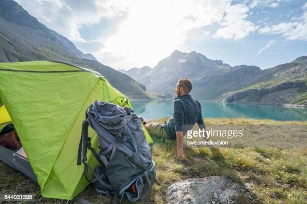 Mâle de randonneur reposant à côté du camping, vue sur le lac